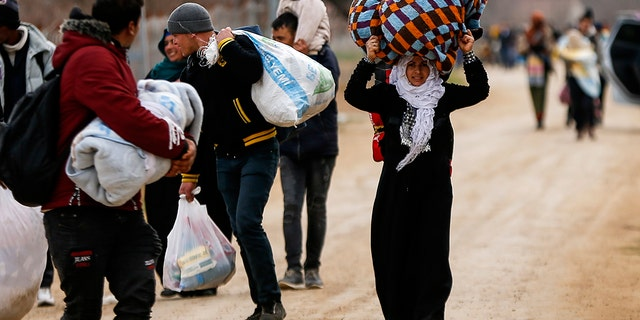 A woman carries her belongings as she walks with other migrants at the Turkish-Greek border in Pazarkule on Wednesday, March 4, 2020. Greek authorities fired tear gas and stun grenades Wednesday morning to repulse a push by migrants to cross its land border from Turkey, as pressure continued along its frontier after Turkey said its own border with Europe was open to whoever wanted to cross. (AP Photo/Emrah Gurel)