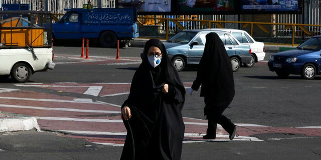 A woman wearing a face mask crosses an intersection in northern Tehran, Iran, Wednesday, March 4, 2020. With deaths spiking in Iran and Italy and infections spreading quickly through Europe, the Mideast and the Americas, countries were considering new drastic measures to curb the new coronavirus that first emerged in China.