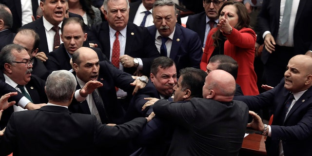 Legislators push each other as a brawl breaks out in Turkey's parliament in Ankara, Turkey, Wednesday, March 4, 2020. A fight broke out in the Turkish parliament between lawmakers from opposing parties during a tense discussion about Turkey's military involvement in northwest Syria. (AP Photo)