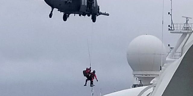 In this photo provided by Michele Smith, a National Guard helicopter delivering virus testing kits lowers crew down to the Grand Princess cruise ship Thursday, March 5, 2020, off the California coast.