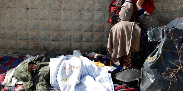 A migrant woman sits as a baby sleeps at an abandoned building in Edirne, near the Turkish-Greek border on Friday, March 6, 2020.