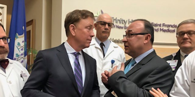 Connecticut Gov. Ned Lamont, second from left, listening to Dr. Danyal Ibrahim of Trinity Health Of New England, second from right, after a news conference about the state's response to the new coronavirus at St. Francis Hospital and Medical Center in Hartford, Conn.