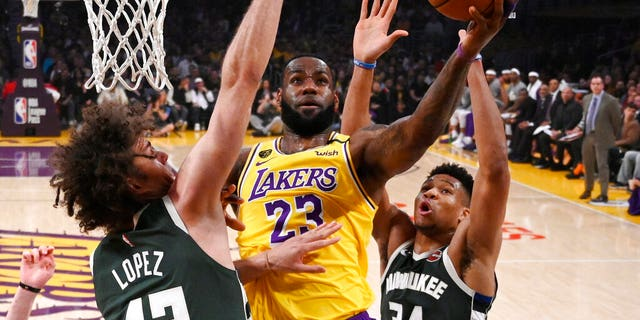 Los Angeles Lakers forward LeBron James, center, shoots as Milwaukee Bucks center Robin Lopez, left, and forward Giannis Antetokounmpo defend during the first half of an NBA basketball game Friday, March 6, 2020, in Los Angeles.