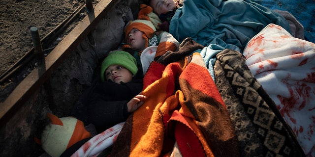 Children from Syria sleep outside at a bus station in Edirne, near the Turkish-Greek border, Saturday, March 7, 2020. Thousands of refugees and other migrants have been trying to get into EU member Greece in the past week after Turkey declared that its previously guarded borders with Europe were open. (AP Photo/Felipe Dana)