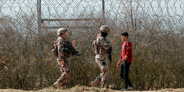 Turkish special police officers patrol by the fence on the Turkish-Greek border in Pazarkule, Turkey, Saturday, March 7, 2020. Thousands of migrants headed for Turkey's land border with Greece after Erdogan's government said last week that it would no longer prevent migrants and refugees from crossing over to EU territory. (AP Photo/Darko Bandic)