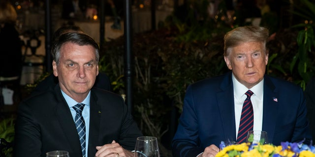President Donald Trump is seated before a dinner with Brazilian President Jair Bolsonaro, left, at Mar-a-Lago, Saturday, March 7, 2020, in Palm Beach, Fla. (AP Photo/Alex Brandon)