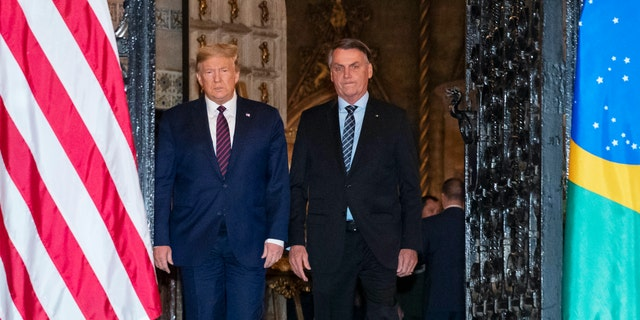 President Donald Trump arrive before a dinner with Brazilian President Jair Bolsonaro at Mar-a-Lago, Saturday, March 7, 2020, in Palm Beach, Fla. (AP Photo/Alex Brandon)