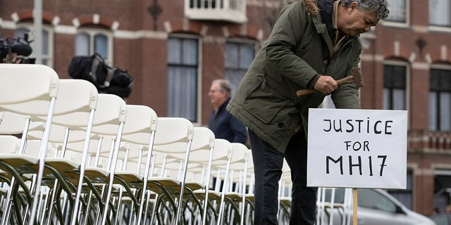 Rob Fredriksz, who lost his son Bryce and his girlfriend Daisy, places a sign next to 298 empty chairs, each chair for one of the 298 victims of the downed Malaysia Air flight MH17, placed in a park opposite the Russian embassy in The Hague, Netherlands, Sunday, March 8, 2020. (AP Photo/Peter Dejong)