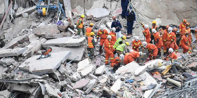 In this photo released by Xinhua News Agency, rescuers search for victims at the site of a hotel collapse in Quanzhou, southeast China's Fujian Province, Sunday, March 8, 2020. Several people were killed and others trapped in the collapse of the Chinese hotel that was being used to isolate people who had arrived from other parts of China hit hard by the coronavirus outbreak, authorities said Sunday. (Lin Shanchuan/Xinhua via AP)