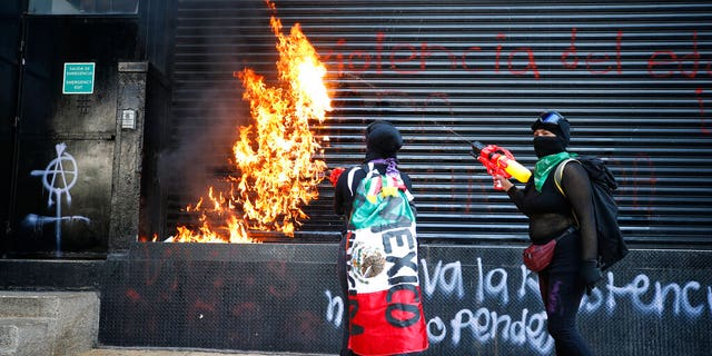 Demonstrators set fire to the entrance of a building during a march for International Women's Day in Mexico City, Sunday, March 8, 2020.