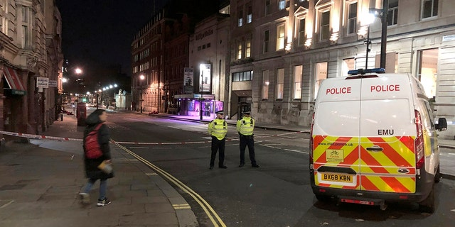 Police stand guard by a cordoned off area after an incident in Westminster, London, early Monday, March 9, 2020. British police say they have shot dead a man who was brandishing two knives near Trafalgar Square in central London. The Metropolitan Police force said Monday that the shooting was not related to terrorism. (Scott D'Arcy/PA via AP)