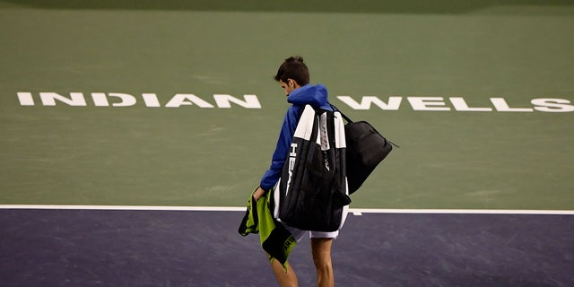 FILE - In this Monday, March 11, 2019, file photo, Novak Djokovic, of Serbia, walks off the court during a rain break in his match against Philipp Kohlschreiber, of Germany, at the BNP Paribas Open tennis tournament in Indian Wells, Calif. The BNP Paribas Open tennis tournament, set to begin Wednesday, March 11, 2020, has been postponed after a case of coronavirus was confirmed in the Coachella Valley. (AP Photo/Mark J. Terrill, File)