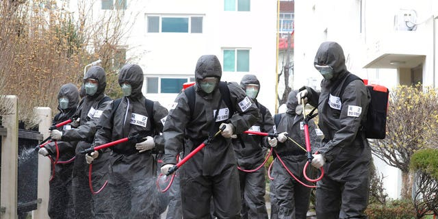 Army soldiers spray disinfectant as a precaution against a new coronavirus at an apartment building in Daegu, South Korea, Monday, March 9, 2020. The world's largest economies delivered more worrisome cues Monday as anxiety over the virus outbreak sent stock and oil prices plunging around the world.