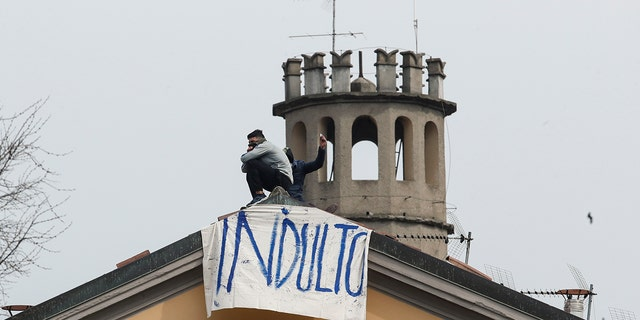Inmates stand by a banner reading in Italian Pardon as they stage a protest against new rules to cope with coronavirus emergency, including the suspension of relatives' visits, on the roof of the San Vittore prison in Milan, Italy, Monday, March 9, 2020. (AP Photo/Antonio Calanni)