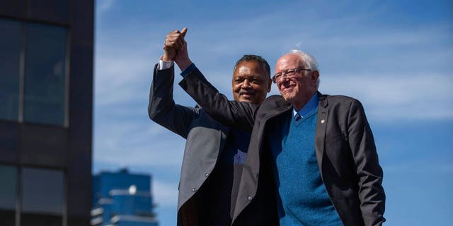 Sen. Bernie Sanders and Rev. Jesse Jackson wave to the crowd at a rally for Sanders at Calder Plaza in Grand Rapids, Michigan on Sunday, March 8, 2020. Michigan's presidential primary is Tuesday. (Anntaninna Biondo/The Grand Rapids Press via AP)