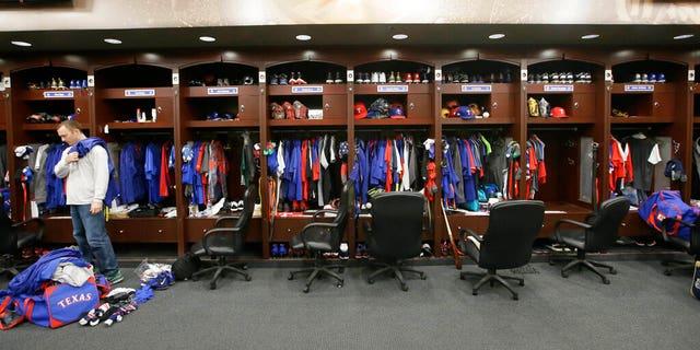 Texas Rangers pitcher Sam Dyson, left, packs a bag in the locker room at the baseball park in Arlington, Texas.