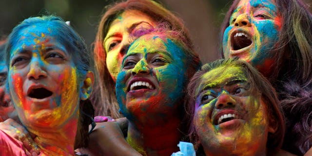Women with their faces smeared with colored powder cheer during celebrations marking the Holi festival in Mumbai, India, Tuesday, March 10, 2020.