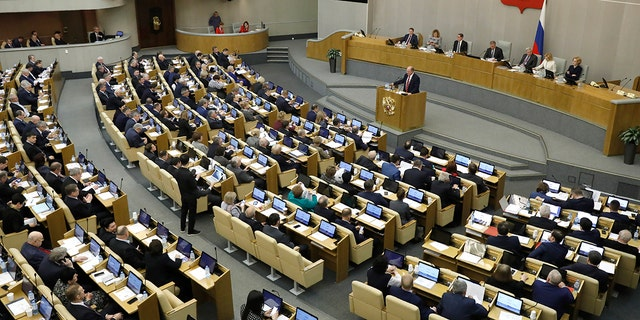 Russian Communist Party leader Gennady Zyuganov, on the podium, speaks during a session prior to voting for constitutional amendments at the State Duma, the Lower House of the Russian Parliament in Moscow, Russia, Tuesday, March 10, 2020. The sweeping reform is widely seen as part of the effort by Putin, who has has to step down in 2024 after having served the two consecutive terms that the country's constitution currently allows, to stay in on power. (AP Photo/Pavel Golovkin)