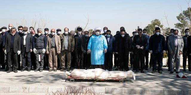 Mourners wearing face masks and gloves pray over the body of former politburo official in the Revolutionary Guard Farzad Tazari, who died Monday after being infected with the new coronavirus, at the Behesht-e-Zahra cemetery just outside Tehran, Iran, Tuesday, March 10, 2020. Iran is the hardest-hit country in the Mideast by the new coronavirus, which sickens but largely doesn't kill those afflicted.