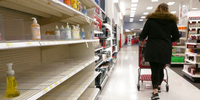 FILE: Shelves that held hand sanitizer and hand soap are mostly empty at a Target in Jersey City, N.J.