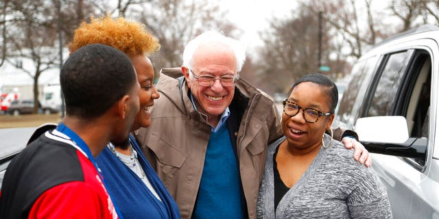 Democratic presidential candidate Sen. Bernie Sanders, I-Vt., visits custodian Davonta Bynes, from left, principal DaRhonda Evans-Stewart and social worker Kim Little outside a polling location at Warren E. Bow Elementary School in Detroit, Tuesday, March 10, 2020. (AP Photo/Paul Sancya)