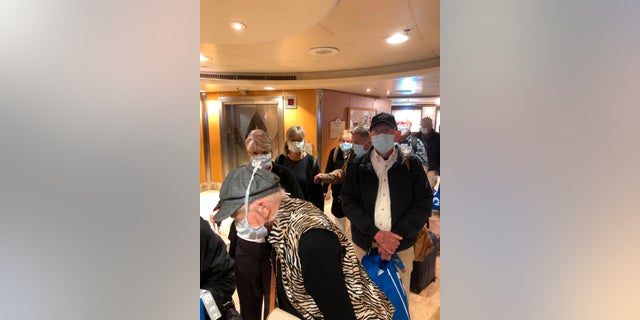 This photo provided by Laurie Miller shows passengers as they get ready to disembark the Grand Princess in Oakland, Calif., Tuesday, March 10, 2020. California Gov. Gavin Newsom urged the state's nearly 40 million residents to avoid sporting events, concerts and large gatherings to prevent the spread of the coronavirus and adamantly warned the elderly to stay away from cruise ships as he pondered measures to restrict cruise travel off the California coast. (Laurie Miller via AP)