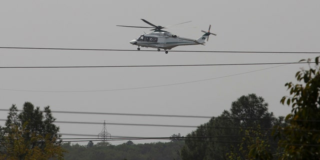 A helicopter hovers over the site of a plane crash in Islamabad, Pakistan, Wednesday, March 11, 2020. Pakistan's air force says one of its fighter jets has crashed in a wooded area near the capital while practicing aerobatic maneuvers. Wednesday's crash was in preparation for National Day celebrations later this month. (AP Photo/B.K. Bangash)