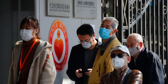 People wearing protective face masks wait in a queue to get temperature check before entering a bank in Beijing, Wednesday, March 11, 2020. For most, the coronavirus causes only mild or moderate symptoms, such as fever and cough. But for a few, especially older adults and people with existing health problems, it can cause more severe illnesses, including pneumonia.