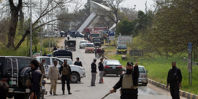 Pakistani authorities cordon off the site of a plane crash in Islamabad, Pakistan, Wednesday, March 11, 2020. Pakistan's air force says one of its fighter jets has crashed in a wooded area near the capital while practicing aerobatic maneuvers. Wednesday's crash was in preparation for National Day celebrations later this month. (AP Photo/B.K. Bangash)
