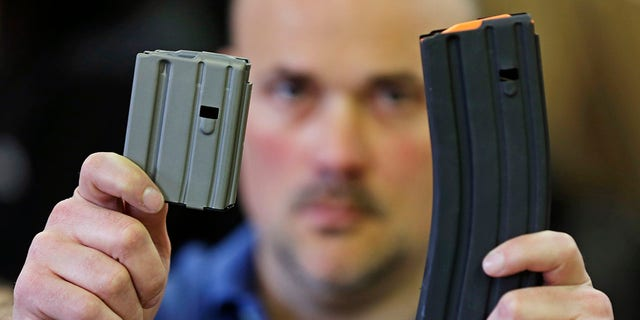 Jonathan Scalise, owner of Ammunition Storage Components, holds up a 10-round, left, and a 30-round magazine that his company manufacturers for the AR-15 rifle in New Britain, Conn., April 10, 2013. Gun rights supporters are suing Connecticut officials over part of a 2013 state gun control law passed after the Sandy Hook school shooting, saying it unconstitutionally bans people from loading more than 10 rounds of ammunition into their firearms. (Associated Press)