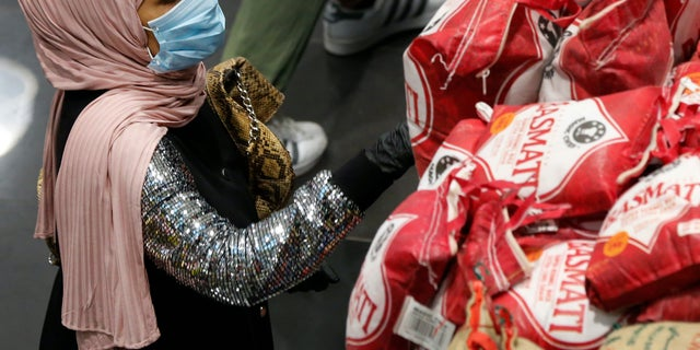 A woman wears a mask and gloves, as she checks products at a supermarket as people begin to stock up on provisions, in Beirut, Lebanon, Wednesday, March 11, 2020. Health Ministry officials say there are more confirmed cases of the coronavirus in Lebanon. The vast majority of people recover from this virus. (AP Photo/Hussein Malla)