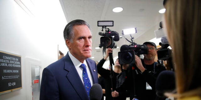 Sen. Mitt Romney, R-Utah, pauses to speak to media as he arrives for a briefing on Capitol Hill in Washington, Thursday, March, 12, 2020, on the coronavirus outbreak. (AP Photo/Carolyn Kaster)