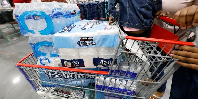 Customers take advantage of the grand opening of a new Costco store in Ridgeland, Miss., to stock up on water and bathroom tissue and cleaning supplies to help deal with coronavirus. (AP Photo/Rogelio V. Solis)