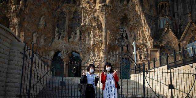 Tourists pose for a photo outside the Sagrada Familia basilica in Barcelona, Spain, Friday, March 13, 2020. The basilica closed its doors to visitors and suspend construction from Friday March 13 to prevent the spread of the new COVID-19 coronavirus. Spain, along with Italy and France, is among the countries worst hit by the virus so far in Europe.