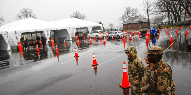 National Guard personnel stand beside a line of motorists waiting for COVID-19 coronavirus infection testing at Glen Island Park in New Rochelle, N.Y., on Friday, March 13, 2020, (AP Photo/John Minchillo)