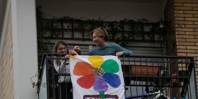 """In this March 13 photo, 8-year hold Flavia is flanked by her mother Silvia as they place a banner reading """"Everything will be alright"""" on the balcony of their apartment in Rome, Italy. (AP Photo/Alessandra Tarantino)"""