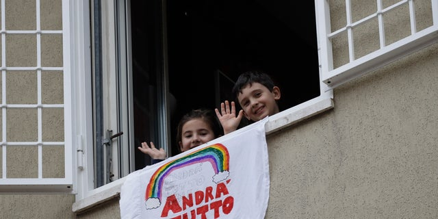 """In this March 13 photo, Francesco and Greta Innominati wave after placing a banner reading """"Everything is gone be all right"""" out of a window of their apartment in Rome, Italy. (AP Photo/Alessandra Tarantino)"""