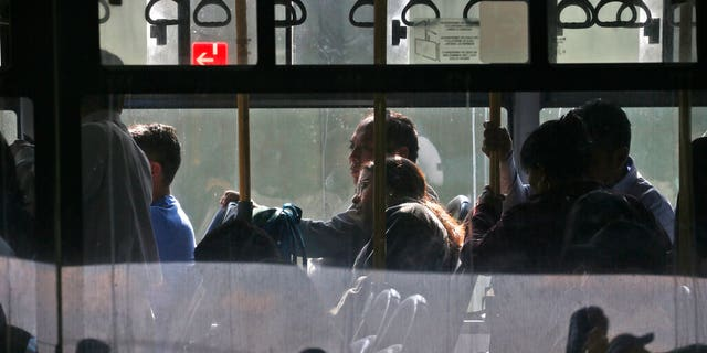 Passengers sit on a bus at the main bus station in Guatemala City, Friday, March 13, 2020.