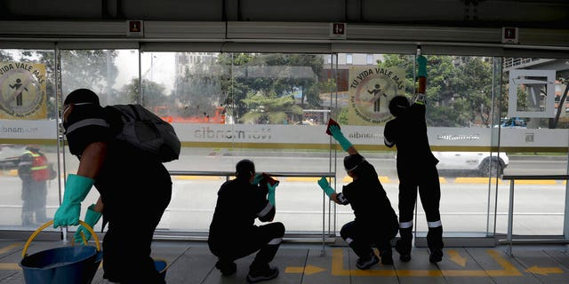 Workers disinfect a bus station in Bogota, Colombia, Friday, March 13, 2020.