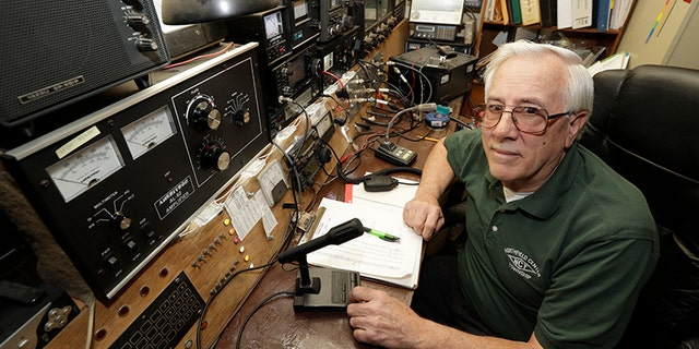 In this Friday, March 13, 2020 photo, Paul Buescher poses by his ham radio, in Northfield Center Township, Ohio. Buescher is one of 32 members of a group in northeastern Ohio that shares a farm packed with enough canned and dehydrated food and water to last for years. (AP Photo/Tony Dejak)