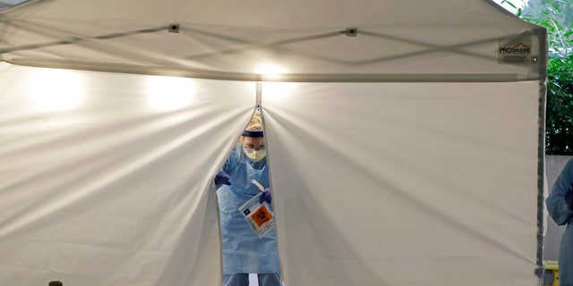 A nurse at a drive up COVID-19 coronavirus testing station in Seattle on March 13. U.S. hospitals are setting up triage tents, calling doctors out of retirement, guarding their supplies of face masks and making plans to cancel elective surgery as they brace for an expected onslaught of coronavirus patients. (AP Photo/Ted S. Warren)