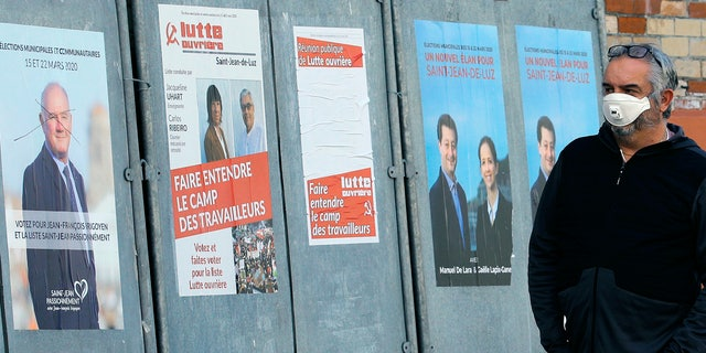 A masked man walks past posters advertising the upcoming local elections, in Saint Jean de Luz, southwestern France, Saturday, March 14, 2020. Authorities fear the new coronavirus and the COVID-19 disease it causes will scare people away from polling stations and have a serious impact on turnout. (AP Photo/Bob Edme)