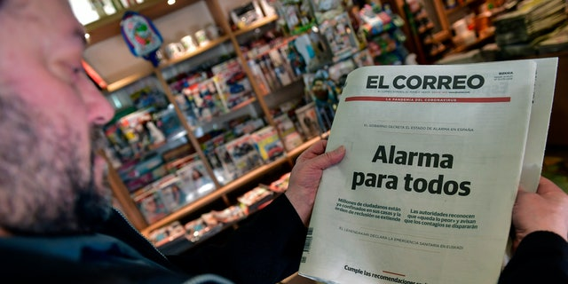 A shows a Spanish basque newspaper with breaking news of coronavirus, ''Alarm for everybody'', in Pamplona, northern Spain, Saturday, March 14, 2020. Spanish Government announced yesterday the alarm state for the whole country. For most people, the new COVID-19 coronavirus causes only mild or moderate symptoms, such as fever and cough, but for some, especially older adults and people with existing health problems, it can cause more severe illness, including pneumonia. (AP Photo/Alvaro Barrientos)