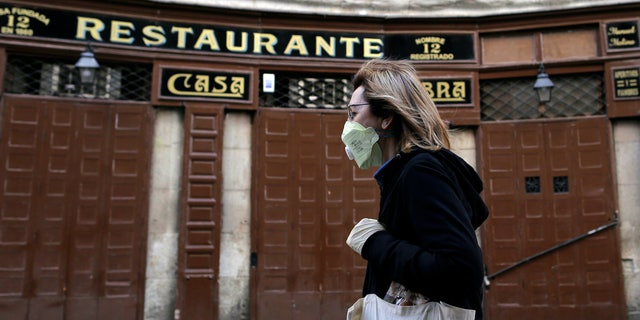 A woman wears a face mask as she walks in front of a closed restaurant in downtown Madrid, Spain, Saturday, March 14, 2020. Spanish Prime Minister Pedro Sanchez said his government will declare a two-week state of emergency on Saturday, giving itself extraordinary powers including the mobilization of the armed forces, to confront the COVID-19 outbreak. For some, especially older adults and people with existing health problems, it can cause more severe illness, including pneumonia. (AP Photo/Manu Fernandez)