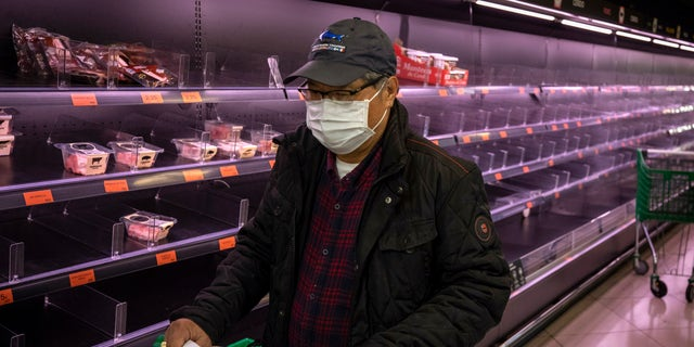 A man wearing a mask walks past empty shelves in a meat market in Barcelona, Spain, Saturday, March 14, 2020. Spain's prime minister has announced a two-week state of emergency from Saturday in a bid to contain the new coronavirus outbreak. For most people, the new coronavirus causes only mild or moderate symptoms. For some, it can cause more severe illness, especially in older adults and people with existing health problems. (AP Photo/Emilio Morenatti)