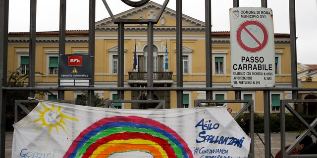 """In this March 14 photo, a banner reading """"Everything will be alright"""" hangs on the main gate of the Spallanzani Hospital for Infectious Diseases, the Italian main hub for coronavirus treatment, in Rome, Italy. (AP Photo/Alessandra Tarantino)"""