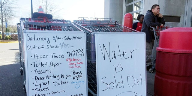A sign outside a Costco warehouse store in Alexandria, Va., advises shoppers which items have sold out over the weekend. As fears of coronavirus grip the nation, Americans are rushing to stock up on staples and disinfectants. (AP Photo/Kevin S. Vineys)