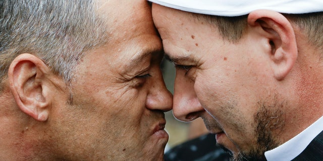 Imam of the Al Noor mosque Gamal Fouda, right, and Tu Tangata motorcycle club president Derek Tait exchange a hongi outside the mosque in Christchurch, New Zealand, Sunday, March 15, 2020. A national memorial in New Zealand to commemorate the 51 people who were killed when a gunman attacked two mosques one year ago has been canceled due to fears over the new coronavirus. (AP Photo/Mark Baker)