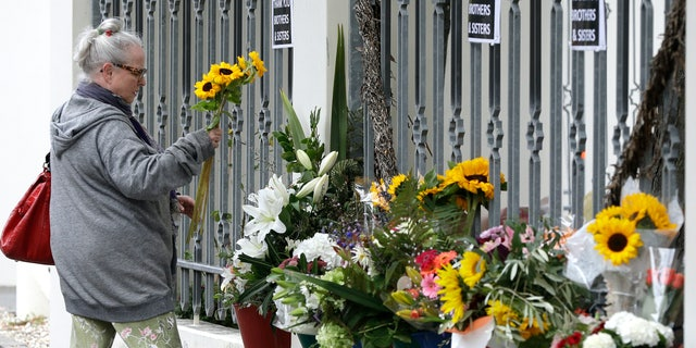 A woman prepares tp lay flowers outside the Al Noor mosque in Christchurch, New Zealand, Sunday, March 15, 2020. A national memorial in New Zealand to commemorate the 51 people who were killed when a gunman attacked two mosques one year ago has been canceled due to fears over the new coronavirus. (AP Photo/Mark Baker)
