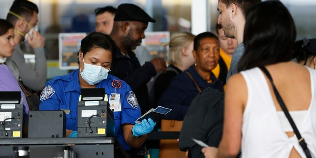 In this March 14 photo, a TSA agent hands a passport back to a traveler as she screens travelers, at a checkpoint inside an airline terminal at John F. Kennedy Airport in New York. (AP Photo/Kathy Willens, File)